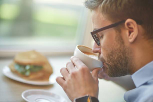 ο άνθρωπος πίνει τον καφέ του στη δουλειά