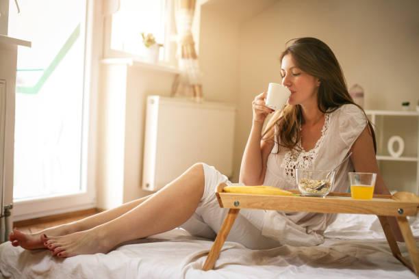 γυναίκα που τρώει πρωινό στο κρεβάτι